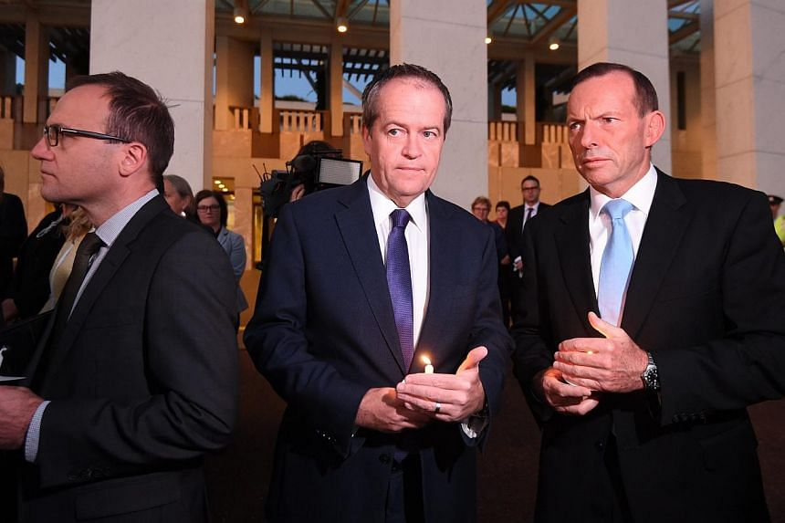 Australian opposition Leader Bill Shorten (centre) and Prime Minister Tony Abbott (right) attending a dawn candlelight vigil at Parliament House in Canberra on March 5, 2015. The vigil was held for Bali Nine ringleaders Myuran Sukumaran and Andrew Ch