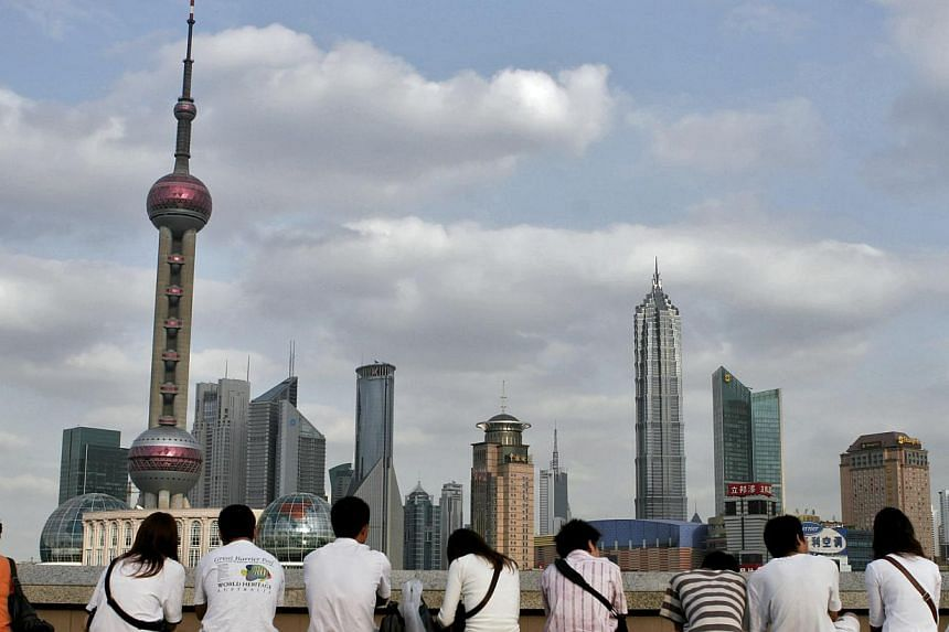 "Visitors gather on Shanghai's famous Bund to look at the skyline of the Pudong financial district across the Huangpu River. China has lowered its 2015 economic growth target to ""around 7 per cent"", state media said on Thursday, as the authorities att"
