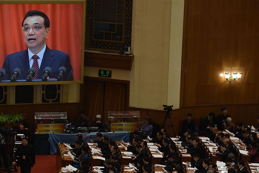 Delegates listening as Chinese premier Li Keqiang (on screen) delivers his work report during the 12th National People's Congress in Beijing on March 5, 2015. -- PHOTO: AFP