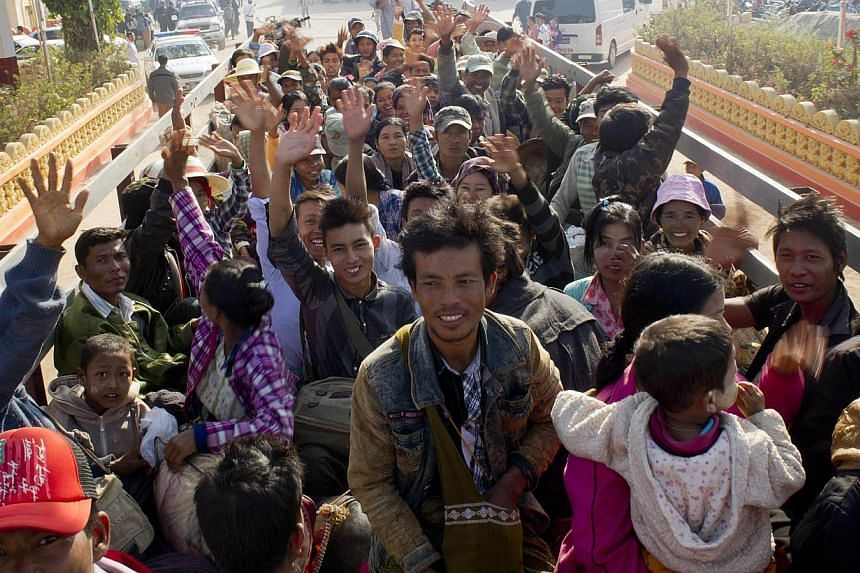 Residents who fled conflict areas near the Myanmar and Chinese border waving onboard a truck transporting them to a refugee camp in Mandalay on Feb 21, 2015. -- PHOTO: AFP