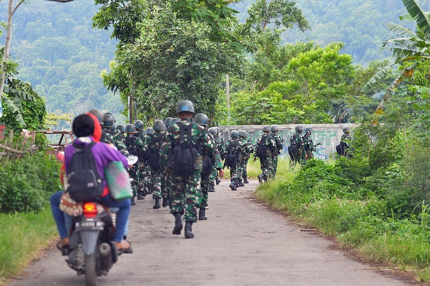 Indonesian military troops marching near Nusakambangan island (in the background) on March 5, 2015, where Australian death row inmates Andrew Chan and Myuran Sukumaran were transferred from Kerobokan prison in Bali. -- PHOTO: AFP