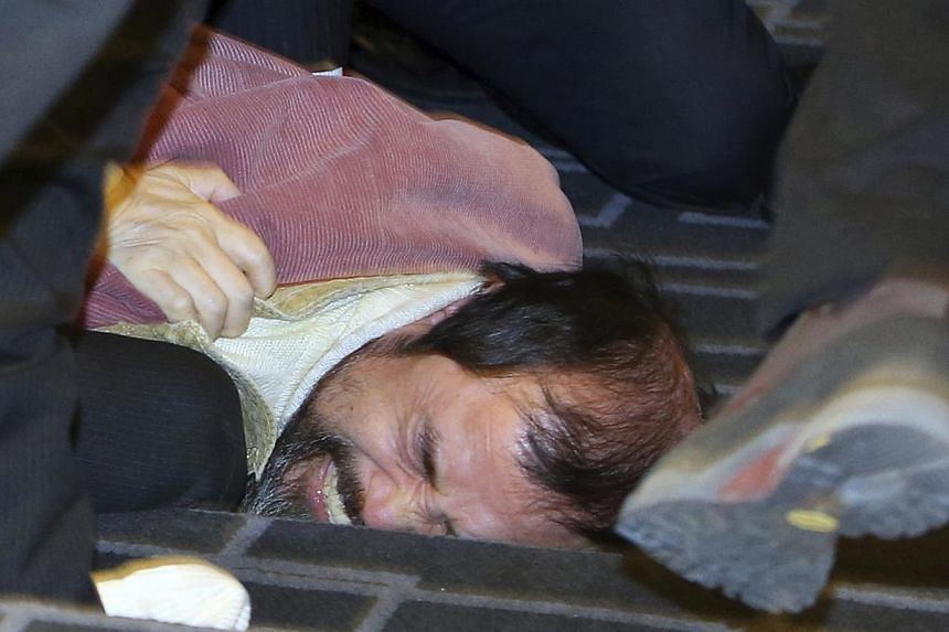 Security personnel detaining a man identified as 55-year-old Kim Ki Jong,who attacked the US ambassador to South Korea Mark Lippert at a public forum, in central Seoul on March 5, 2015. The US ambassador to South Korea was slashed in the face b