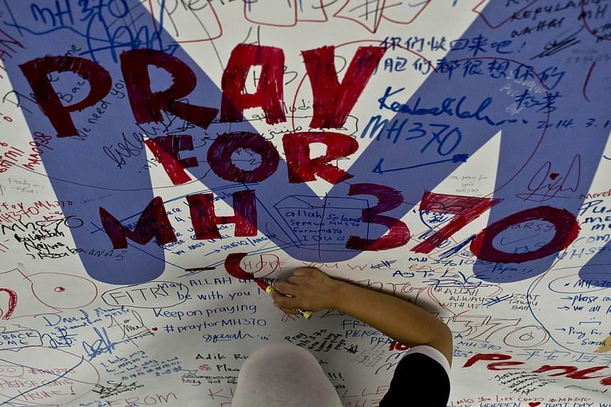 A file photo taken on March 14, 2014 shows a Malaysia Airlines employee writing a message expressing prayers and good wishes for passengers onboard missing Malaysia Airlines Flight MH370 at Kuala Lumpur International Airport in Sepang. -- PHOTO: AFP