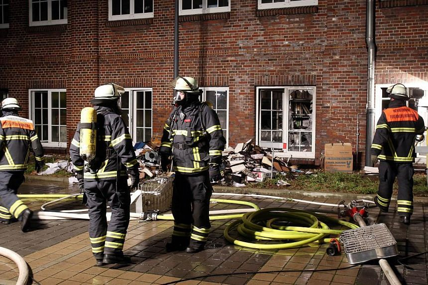 Firefighters outside German regional newspaper Hamburger Morgenpost in Hamburg, northern Germany, on Jan 11, 2015, following an arson attack. German police on Wednesday temporarily detained nine suspects over a January arson attack on a newspape