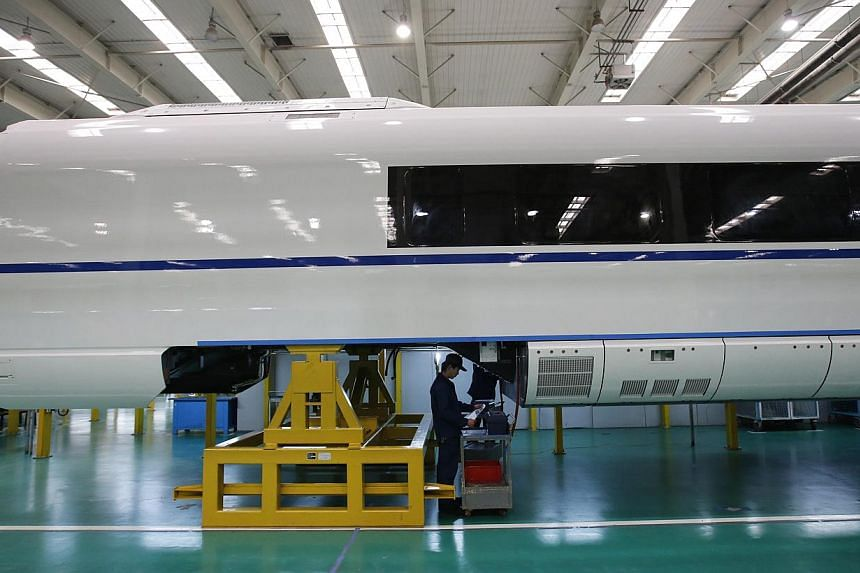 An employee works on a final assembly line for a high speed train model in Hebei.China announced its projected growth rate for 2015 at 7 per cent, after clocking the slowest growth in 24 years last year (at 7.4 per cent). As a result, much is r