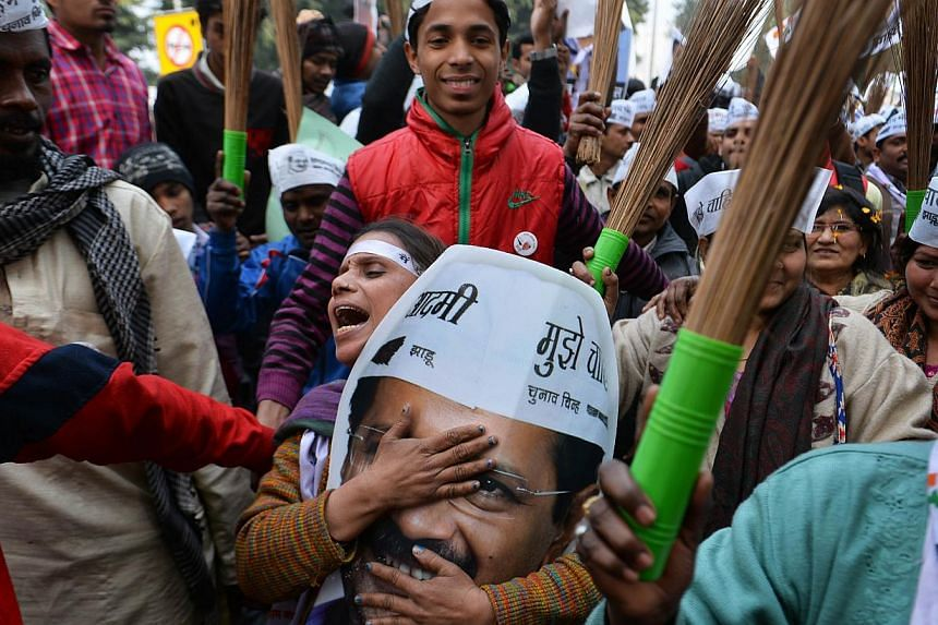 Voters in New Delhi showing their support for the Aam Aadmi Party in January. Party chief Arvind Kejriwal's picture is a favourite, but many carry a broom, the party's election symbol in the Delhi elections.