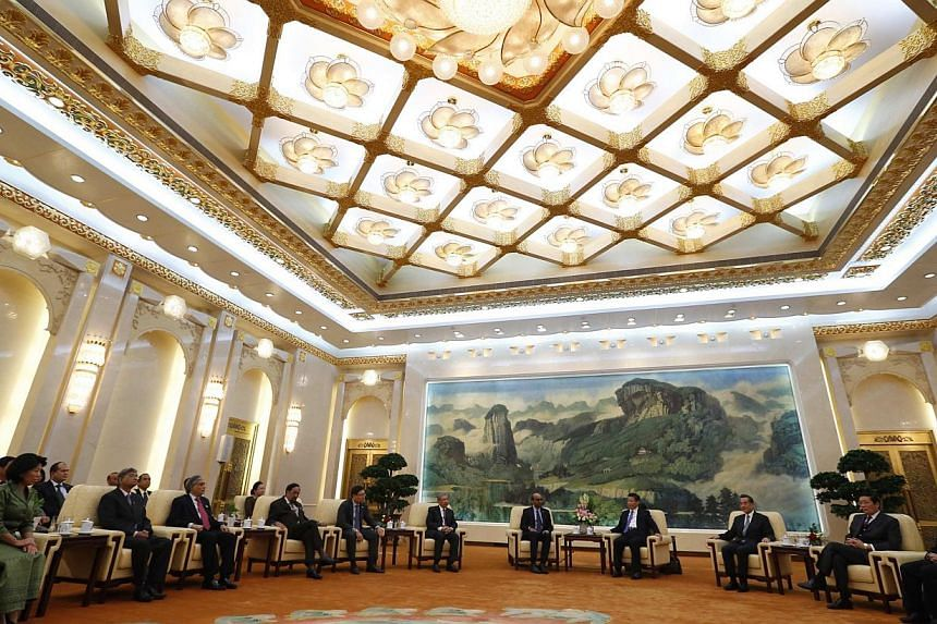 China's President Xi Jinping (fourth from right) with guests at the Asian Infrastructure Investment Bank launch ceremony in the Great Hall of the People in Beijing last October. US First Lady Michelle Obama with Japanese Prime Minister Shinzo Abe in