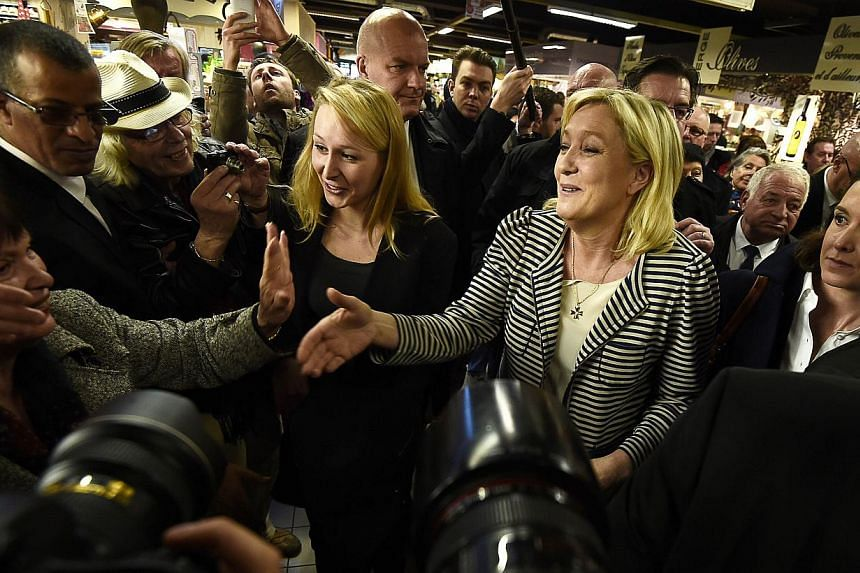 The president of the far-right National Front (FN) party, Ms Marine Le Pen (right), working the crowd on March 17, 2015, at a market in the southern French city of Avignon. Fear of immigration and anger about elite corruption have bolstered the FN -