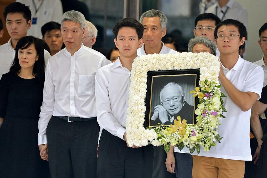 Mr Lee Kuan Yew's grandsons Li Shengwu (left) and Li Haoyi hold up his portrait while surrounded by other family members and close friends at the Mandai Crematorium for Mr Lee's funeral service on March 29, 2015.