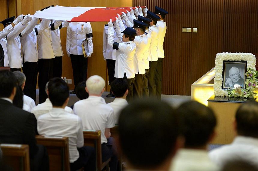 The pallbearers folding the Singapore flag after laying the casket of Mr Lee Kuan Yew in the ceremonial hall at the Mandai Crematorium for the private family funeral on March 29, 2015.