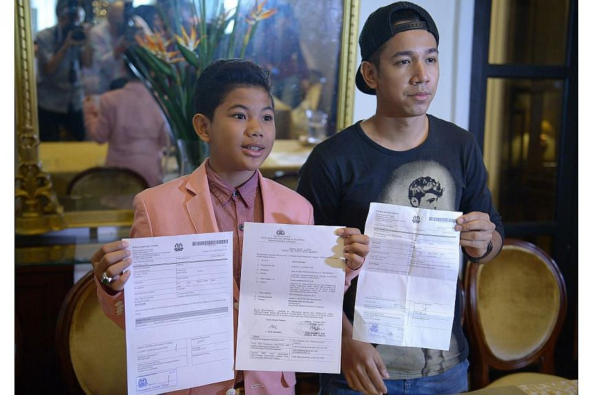 Tegar (left) and local singer Sufie Rashid showing the police reports lodged in Singapore and Indonesia at the press conference. -- ST PHOTO: DESMOND WEE