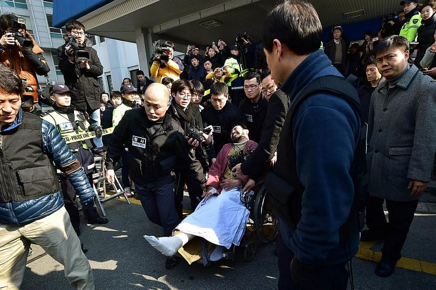 South Korean policemen carry Kim Ki Jong (on wheelchair), who attacked US Ambassador Mark Lippert with a knife, as he leaves a police station for a court in Seoul on March 6, 2015. South Korean prosecutors formally charged Kim with attempted mur