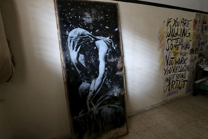 The doorway of a destroyed house, which was painted by British street artist Banksy, is seen inside the gallery of a local Palestinian artist after he bought it from the house's owner, in Khan Younis in the southern Gaza Strip on April 1, 2015. -- PH
