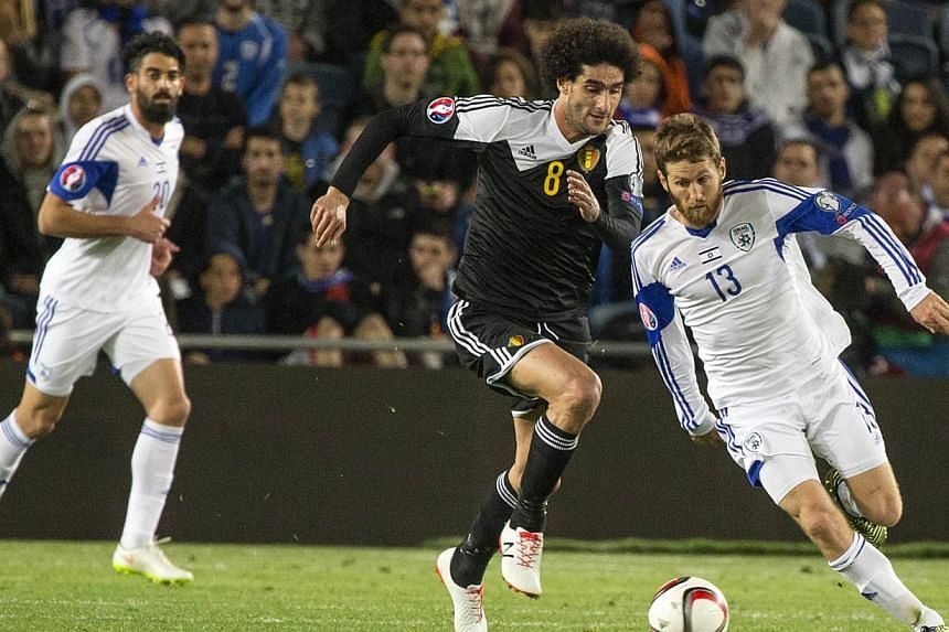 Israel's midfielder Sheran Yeini (right) vying with Belgium's midfielder Marouane Fellaini during their Euro 2016 qualifying football match match between Israel and Belgium on March 31, 2015. -- PHOTO: AFP