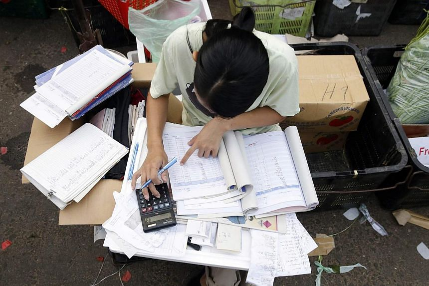 A trader completes paperwork at a wet market in Kuala Lumpur on March 3, 2015. Some Singapore firms expect a short-term hit to sales as prices rise after a major spending spree by Malaysians in the weeks before the GST took effect. -- PHOTO: REUTERS