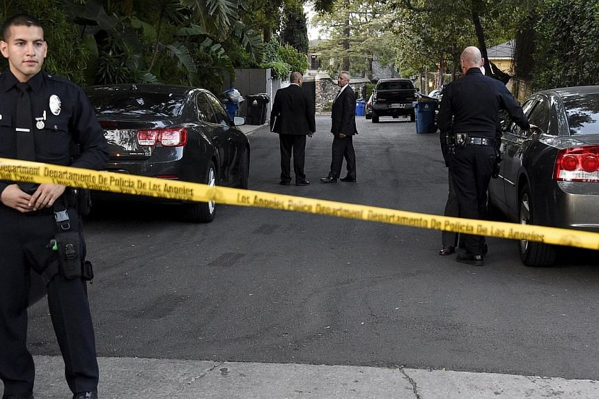 Los Angeles Police Department officers and investigators gather on a street leading to the house of Andrew Getty, 47, the grandson of Getty oil founder J. Paul Getty, in the Hollywood Hills section of Los Angeles, California on March 31, 2015. -- PHO