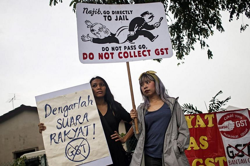 Malaysian protestors hold a poster reading 'No GST' as they protest outside custom office at Kelana Jaya,suburb of the capital Kuala Lumpur, Malaysia on March 23, 2015. More than 100 protestors from NGO's and political parties staged a protest outsid