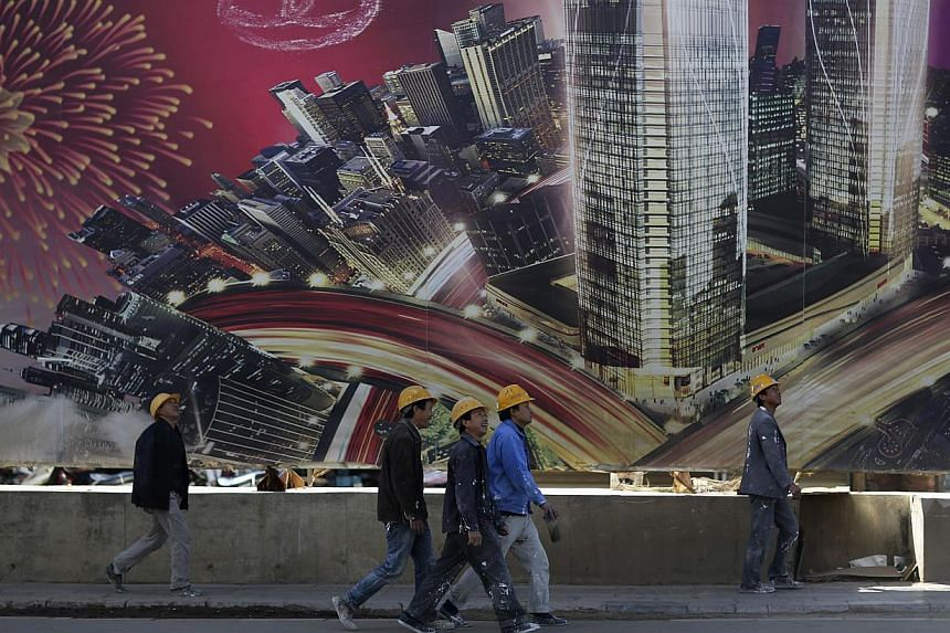 Construction workers walking past an advertisement board in Kunming, Yunnan province on Jan 25, 2015. -- PHOTO: REUTERS