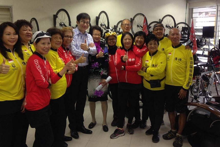 The Concern and Care Society cyclists together with chief executive David Lee (centre, in long-sleeved shirt) and chairman Margaret Wee (centre, in dress with floral prints). -- ST PHOTO: CHONG ZILIANG