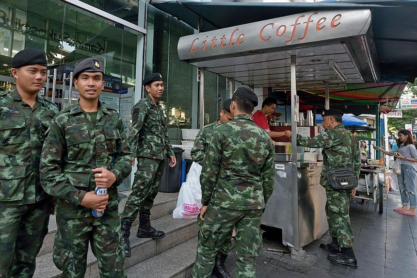 Thai soldiers standing along the pavement during a crackdown on sidewalk vendors along a main road in Bangkok on Nov 1, 2014. Thailand has repealed martial law some 10 months after it was imposed, amid a protracted political crisis. -- PHOTO: AFP