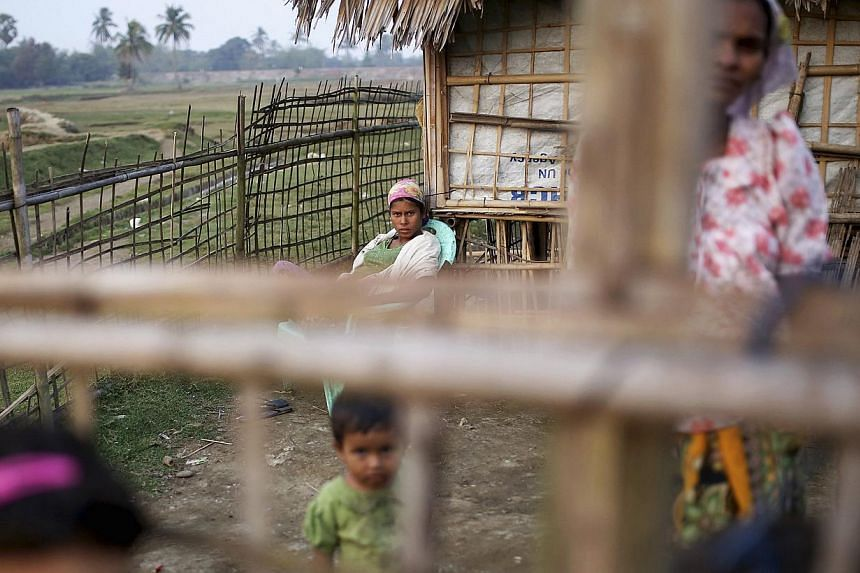 Internally displaced Rohingya women and children look from behind the fence of their temporary home at Thae Chaung IDP camp on the outskirts of Sittwe on Feb 15, 2015. Myanmar authorities have begun collecting temporary identification cards from