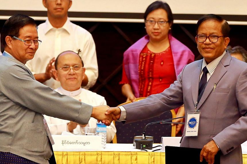 Union Peace-making Work Committee vice-chairman Aung Min (left) shaking hands with Nationwide Ceasefire Coordination Team leader Naing Han Tha after they signed the draft ceasefire pact yesterday. Myanmar President Thein Sein witnessed the signing of