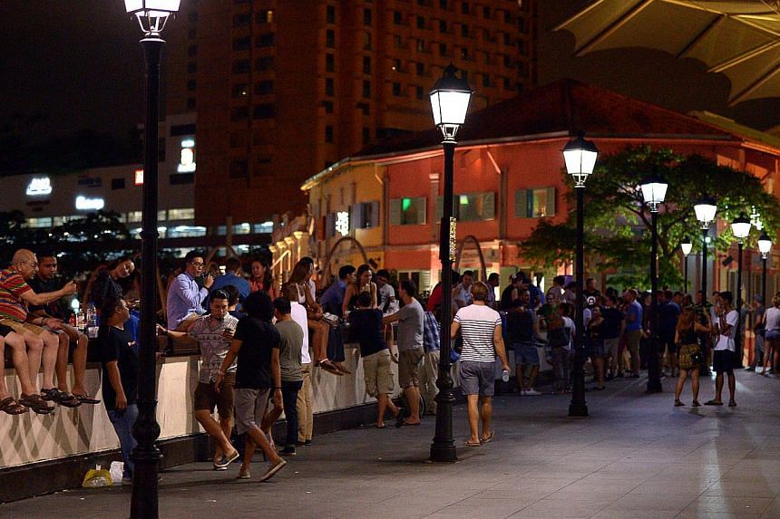 At least 200 people were seen on Read Bridge at Clarke Quay after midnight and drinking even though the new Liquor Control (Supply and Consumption) Act bans drinking in all public places from 10.30pm to 7am. -- ST PHOTO: DESMOND WEE'