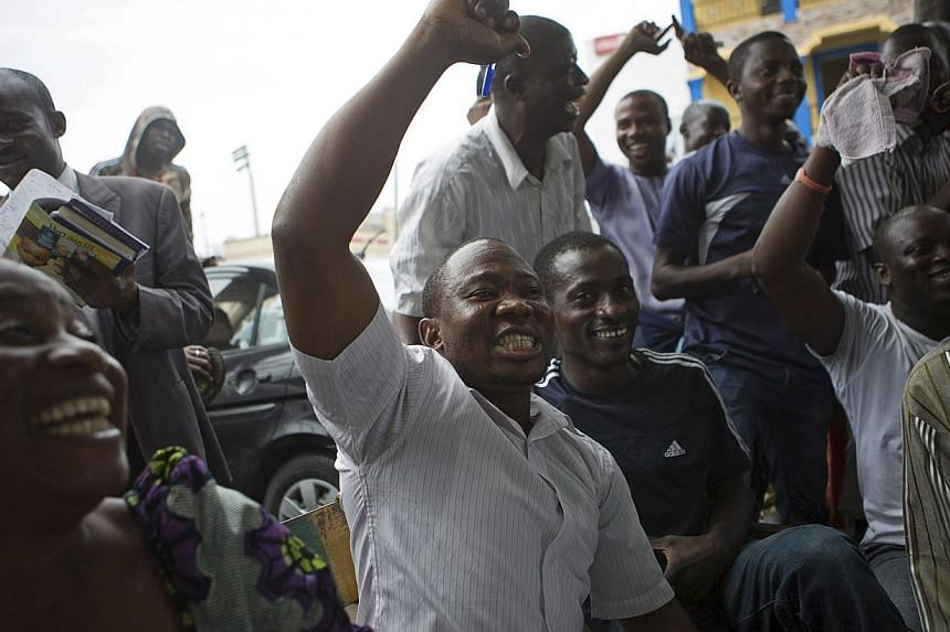 Supporters of presidential candidate Muhammadu Buhari cheer as they watch news coverage of election results favourable to them on a street in Lagos, March 31, 2015. -- PHOTO: REUTERS