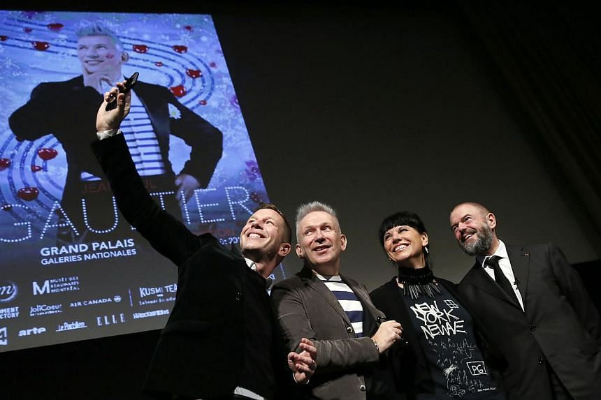 French fashion designer Jean-Paul Gaultier (C), flanked by The Grand Palais Museum president Jean-Paul Cluzel (R), the curator of museum des Beaux arts of Montreal, Nathalie Bondil and the curator of the exhibition Thierry-Maxime Loriot (L), pose for