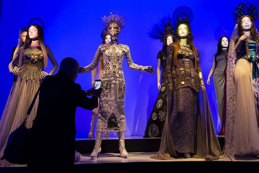 A visitor looks at creations by French fashion designer Jean-Paul Gaultier displayed as part of the Jean-Paul Gaultier retrospective held at the Grand Palais in Paris, France, 30 March 2015. -- PHOTO: EPA