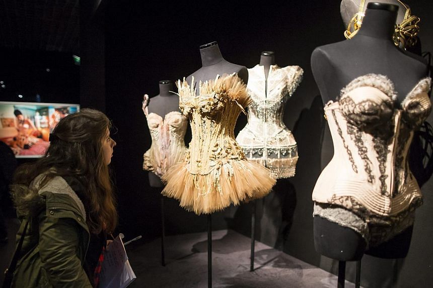 A visitor looks at creations by French fashion designer Jean-Paul Gaultier displayed as part of the Jean-Paul Gaultier retrospective held at the Grand Palais in Paris, France, 30 March 2015.-- PHOTO: EPA