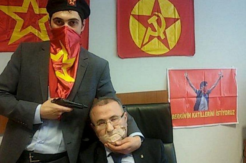 A gunman poses with Prosecutor Mehmet Selim Kiraz with a gun on his head after being taken hostage in his office in a court house in Istanbul March 31, 2015. A senior Turkish prosecutor and his two hostage-takers were killed on Tuesday when security
