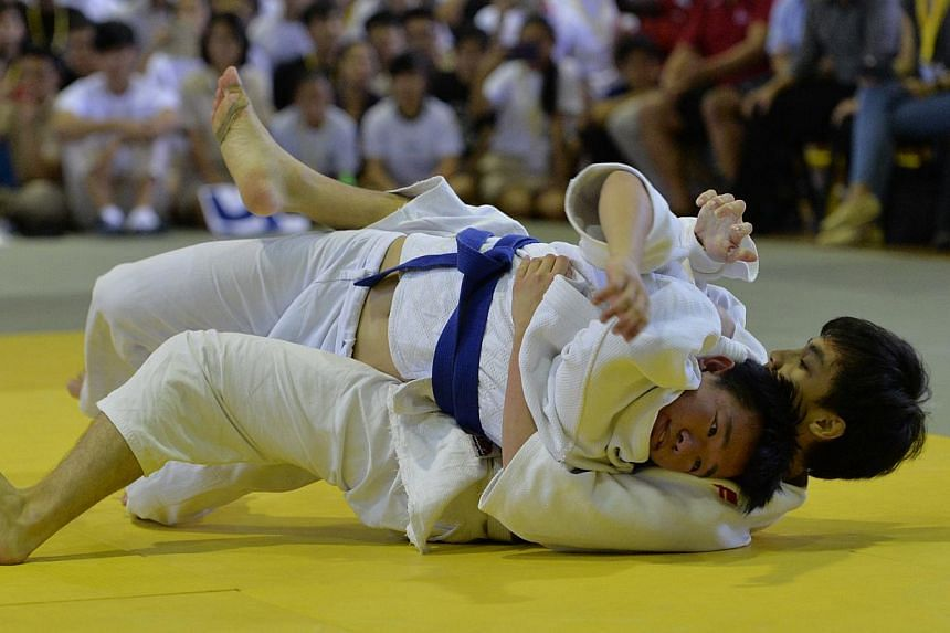 Wesley Kam (with blue belt) from Nanyang Junior College competing with Ong Jia Xiang from Raffles Institution, in the 'A' Division National Team Judo Championship Finals. -- ST PHOTO: CAROLINE CHIA