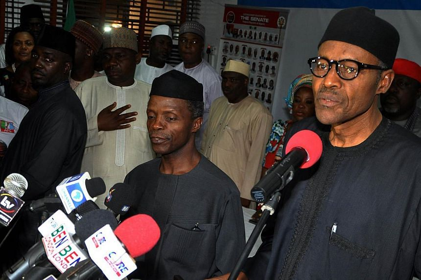 Nigerian president-elect Muhammadu Buhari (right) reads his acceptance speech in Abuja on April 1, 2015. Mr Buhari congratulated outgoing President Goodluck Jonathan for peacefully relinquishing power on Wednesday, a day after becoming the first poli
