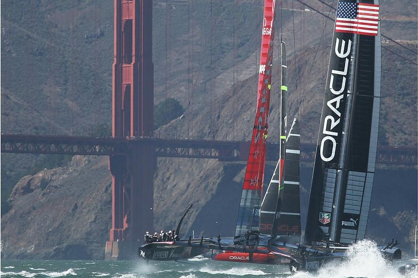Oracle Team USA and Emirates Team New Zealand racing by the Golden Gate Bridge in the 19th race of the America's Cup on Sept 25, 2013. America's Cup teams have voted to use smaller boats in the historic contest to save money, even though the dec
