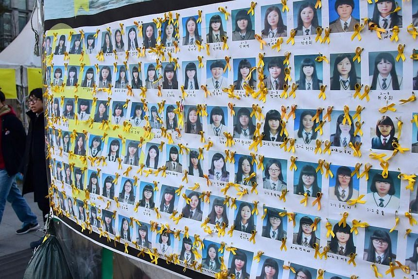"Pedestrians walk past portraits of the victims of the sunken South Korean ferry ""Sewol"" at Gwanghwamun square where relatives of the victims have been sitting in protest against the government, in Seoul on Jan 8, 2015. -- PHOTO: AFP"