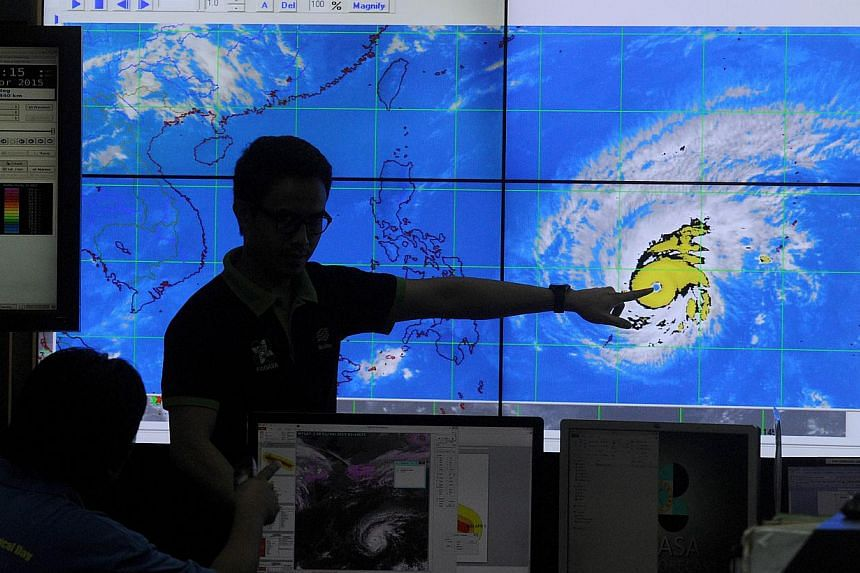 Meteorologists from the Philippine Atmospheric, Geophysical and Astronomical Services Administration (PAGASA) monitor and plot the direction of super typhoon Maysak at PAGASA headquarters in suburban Manila on April 1, 2015. -- PHOTO: AFP