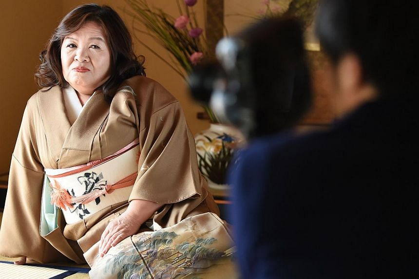 Ms Yasue Tomita, 61, sitting on a tatami floor while posing for a photographer as she makes her debut as a porn actress at a studio in Tsurugashima, Saitama prefecture, on March 17, 2015. Dressed in a kimono and kneeling silently on a tatami mat floo