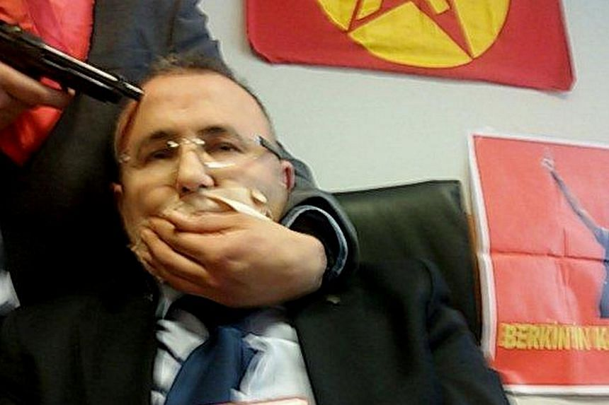 In this news agency photo, an alleged millitant from the Turkish Marxist-Leninist left wing organisation, the DHKP-C, holds a gun to the head of prosecutor Mehmet Selim Kiraz in Istanbul on March 31, 2015. A senior Turkish prosecutor and his two host
