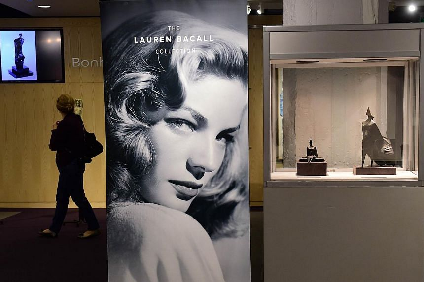 An image of actress Lauren Bacall is displayed next to Lynne Chadwick's Marquette ll Walking Woman statue during a media preview in Los Angeles on Feb 26, 2015, at Bonhams Los Angeles. -- PHOTO: AFP