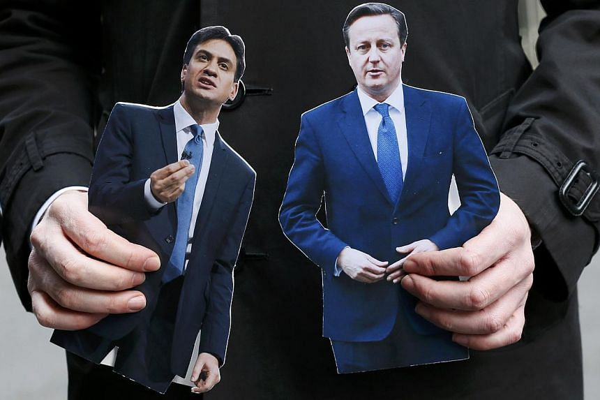 A journalist standing in Downing Street holding cardboard cutouts of Britain's Prime Minister David Cameron (right) and Ed Miliband, the leader of the opposition Labour Party, in central London on March 18, 2015. Mr Cameron will face off against six