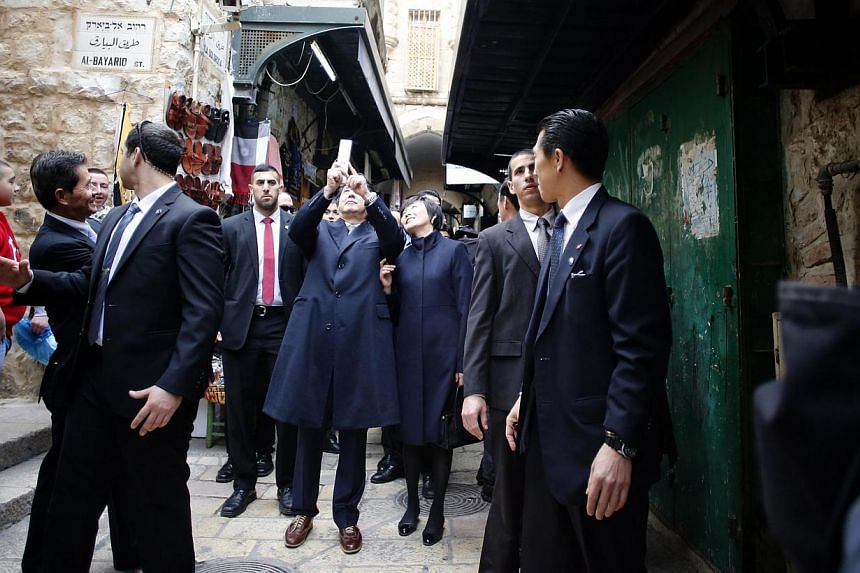 "Japanese Prime Minister Shinzo Abe (middle) taking a selfie with his wife Akie during a visit to the Old City of Jerusalem on Jan 19, 2015. Mr Abe's party is offering a chance for people to take selfies with the premier by installing a ""puri-kura"" (p"