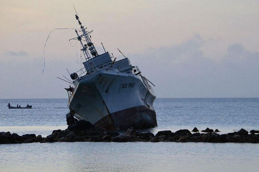 In this March 29, 2015 photo, a ship is seen resting on rocks after it ran aground during storms brought on by Super Typhoon Maysak near the coastal village of Neauo on the island of Weno in the Micronesian state of Chuuk. -- PHOTO: AFP