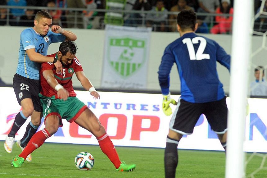 Morocco's Mzehdi Ben Attia (centre) fights for the ball against Uruguay's Martin Silva (left) as Moroccan goalkeeper Mounir Mohamdi looks on during a friendly football match in Agadir, Morocco, on March 28, 2015. The Court of Arbitration for Spo