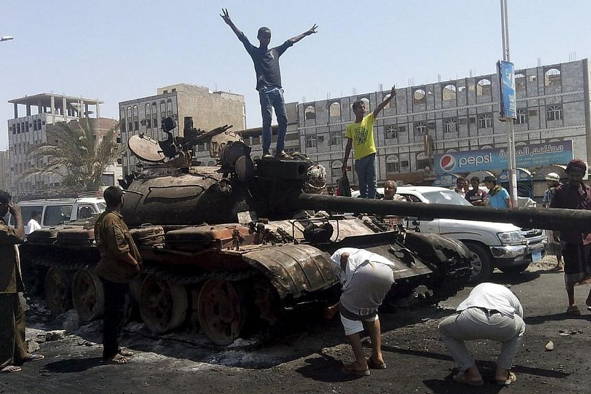 Boys stand on a tank burned during clashes on a street in Yemen's southern port city of Aden March 29, 2015.Rebel forces seized Yemeni President Abedrabbo Mansour Hadi's palace in his former southern refuge of Aden on Thursday, April 2, a senio