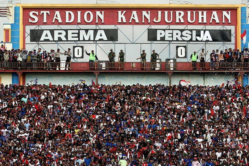 The Aremania, as fans of Indonesian Super League (ISL) football club Arema Malang are called, showing their support during an ISL match against Persija on Oct 11, 2009, at the Kanjuruhan Stadium in Malang, Indonesia. The league has been plagued by pr