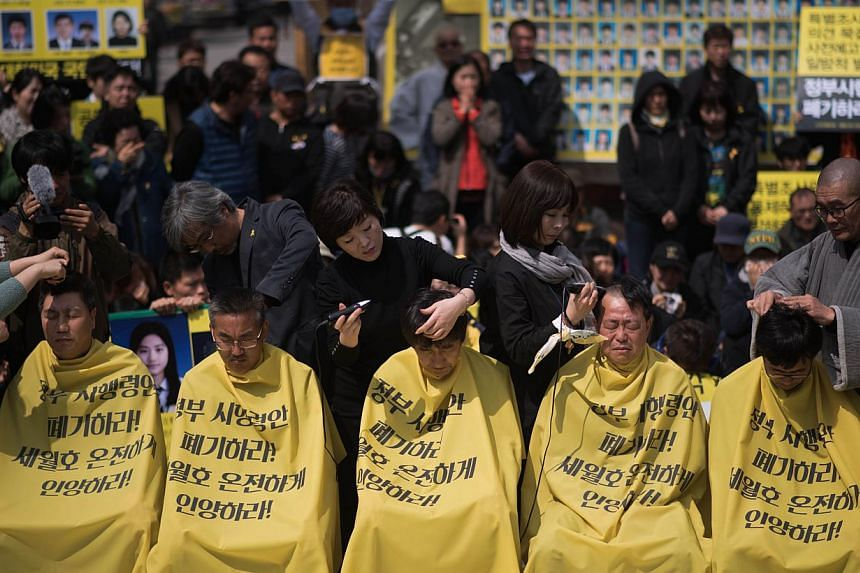 Relatives of victims of the Sewol ferry accident have their heads shaved during a protest ahead of the anniversary of the disaster, in Seoul on April 2, 2015.Around 50 mothers and fathers of victims of the disaster had their heads shaved to pus
