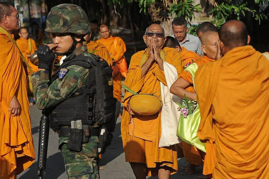 A Thai soldier provides security as Buddhist monks collect alms to mark Princess Maha Chakri Sirindhorn's birthday in Narathiwat, southern Thailand on April 2, 2015. A sweeping new security measure in Thailand that has replaced martial law does
