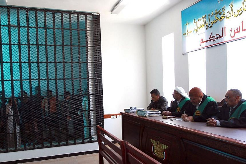 Suspected Al-Qaeda militants stand behind bars during a hearing at the appeals court in the Yemeni capital Sanaa on Feb 10, 2015.Al-Qaeda militants stormed a prison in south-eastern Yemen on Thursday, freeing several hundred inmates including o