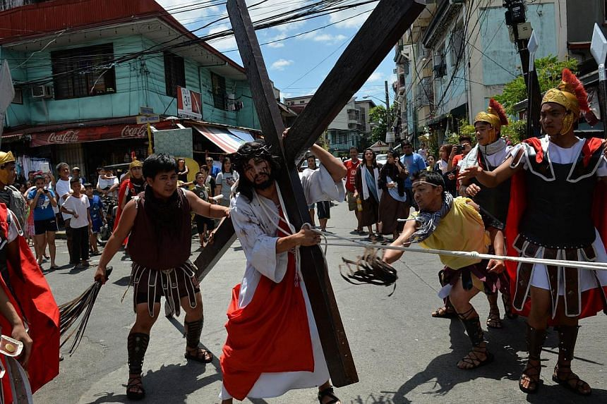 A man (centre), acting as Jesus, carries a wooden cross as others, acting as Roman soldiers, whip him as they re-enact the passion and death of Jesus as part of Lenten observance in Manila on April 2, 2015. --PHOTO: AFP